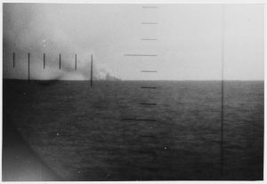 Enemy ship burns on the horizon after being torpedoed by the Pompano