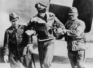 US Army Air Force officer, blindfolded by his captors, is led from a Japanese transport plane
